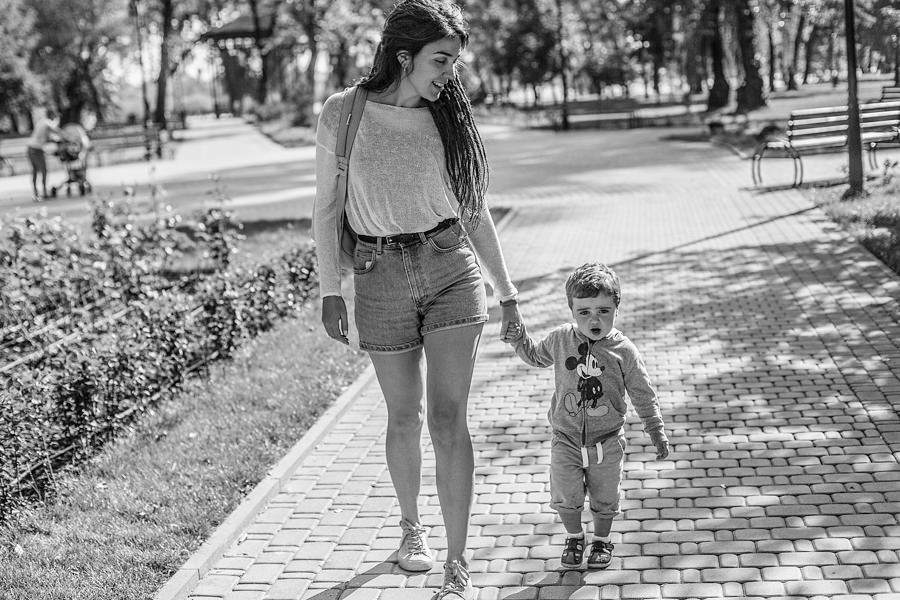 mother is walking with her son in a park, smiling to him