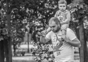 son is sitting in father's shoulders, they are walking in a funny way