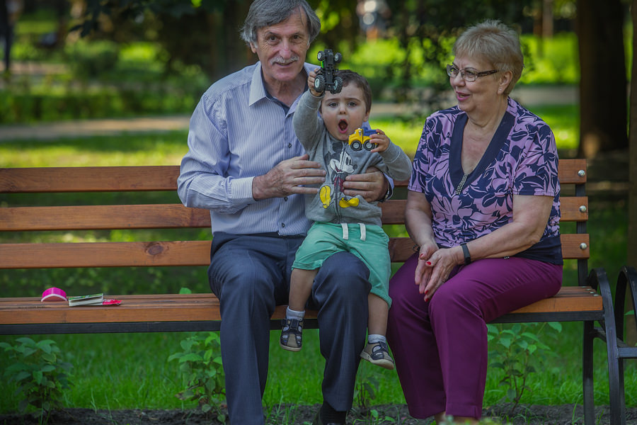 little boy is holding a toy car sitting in a park bench with his grandmother and grandfather