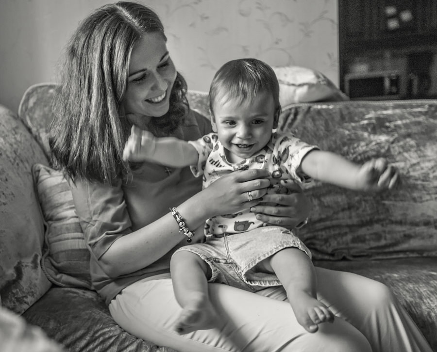 mother and a little boy smiling on a couch